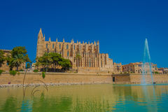 PALMA DE MALLORCA, SPAIN - AUGUST 18 2017: Beautiful view of Cathedral of Santa Maria of Palma La Seu in a gorgeous blue. Sky, with an artifical pond with a Royalty Free Stock Photos