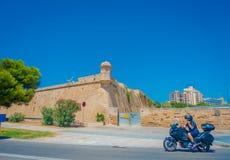 PALMA DE MALLORCA, SPAIN - AUGUST 18 2017: Motorbike traveling near of Cathedral of Santa Maria of Palma La Seu in a. Gorgeous blue sky, in Palma de Mallorca Royalty Free Stock Images