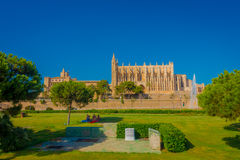 PALMA DE MALLORCA, SPAIN - AUGUST 18 2017: Unidentified people sitting in a grass in the park near of the Cathedral of Royalty Free Stock Image