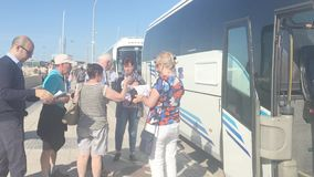 Group of tourists outside a bus on a sunny day. PALMA DE MALLORCA, SPAIN - MAY 23, 2019: Group of tourists outside a bus on a sunny day on May 23, 2019 in stock video footage