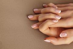 Palma femenina joven Manicura hermosa del encanto Estilo francés Pulimento de clavo Cuide sobre las manos y los clavos, piel limp fotos de archivo libres de regalías