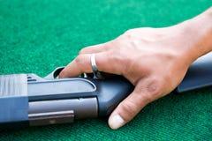 Palma maschio che pone sopra il fucile ad aria compressa Immagine Stock