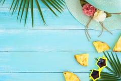 Palma opuszcza na drewnianej deski błękitnym kolorze, słomiany kapelusz, ananasów plasterki i okulary przeciwsłoneczni, Zdjęcie Royalty Free
