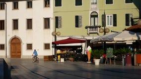PALMANOVA, ITALIA - 11 AGOSTO 2017 Equipaggi la bicicletta di guida vicino ai caffè della via ed alle vecchie costruzioni Immagini Stock