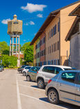 Palmanova,  Italy:  Old water tower and cars parked near old colored houses in sunny spring day Royalty Free Stock Images