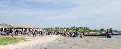 Palmarin, Senegal - October 30, 2013: Many people on beach with fish market and fishing boats, return of the fishermen. Palmarin, Senegal - October 30, 2013 Stock Images