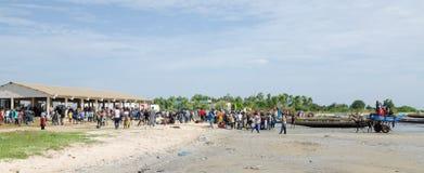 Palmarin, Senegal - Oktober 30, 2013: Vele mensen op strand met vissenmarkt en vissersboten, terugkeer van de vissers Stock Afbeeldingen