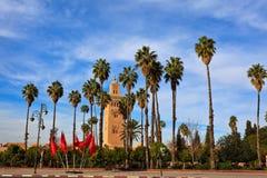 Palmas altas e bandeiras marroquinas pelo minarete imagens de stock royalty free