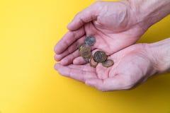 Palmas do ` s dos homens com moedas Falta de dinheiro Salário baixo fotografia de stock royalty free