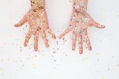 Palmas femeninas en confeti del oro y de la plata Foto de archivo