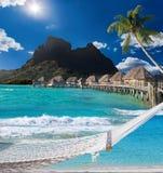 Palmas, hamaca y océano. Bora-Bora. Polinesia Imagen de archivo libre de regalías