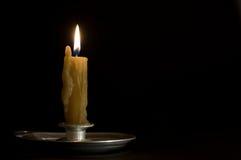 Palmatoria antigua del metal con la vela ardiente Imagenes de archivo