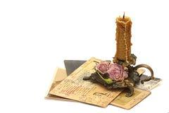 Palmatoria de bronce antigua, vela y fotos viejas Fotografía de archivo