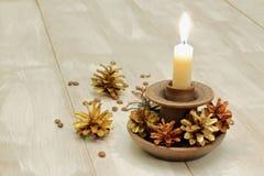 Palmatoria de cerámica y vela blanca ardiendo de la cera, conos multicolores del pino y granos de café en fondo de madera ligero foto de archivo libre de regalías