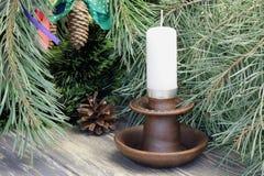 Palmatoria de la arcilla con una vela de la cera, un abeto y conos blancos del pino en el fondo de las agujas del pino Fondo de m imagen de archivo libre de regalías