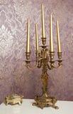 Palmatoria de oro con cinco velas en la tabla blanca Foto de archivo libre de regalías