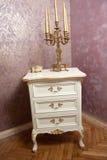 Palmatoria de oro con cinco velas en los muebles de madera blancos delante de la pared texturizada lujosa Imagen de archivo