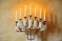Palmatoria vieja con las velas ardientes Imagenes de archivo