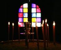 Palmatoria y velas en la luz oscuro de la iglesia Imagen de archivo