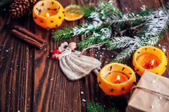 Palmatorias hechas de mandarines con las ramas, los juguetes y los presentes del abeto en la tabla de madera Fondo de la Navidad  Fotos de archivo