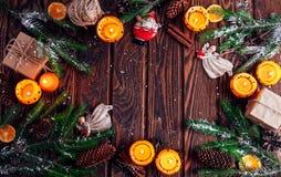 Palmatorias hechas de mandarines con las ramas, los juguetes y los presentes del abeto en la tabla de madera Fondo de la Navidad  Foto de archivo libre de regalías