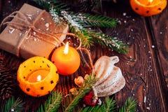 Palmatorias hechas de mandarines con las ramas, los juguetes y los presentes del abeto en la tabla de madera Fondo de la Navidad  Imagen de archivo libre de regalías