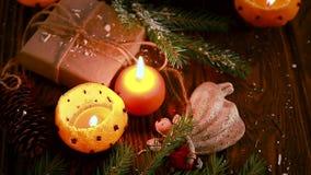 Palmatorias hechas de mandarines con las ramas, los juguetes y los presentes del abeto en la tabla de madera Fondo de la Navidad  almacen de metraje de vídeo