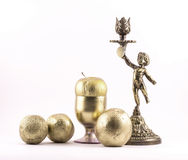 Palmatorias pintadas de oro con la imagen de un muchacho y elementos, una manzana, un vidrio y naranjas florales en un fondo blan Fotografía de archivo libre de regalías