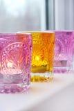 Palmatorias rosadas y amarillas de cristal en el alféizar blanco Fotos de archivo libres de regalías