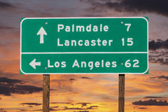 Palmdale, Lancaster and Los Angeles Highway Sign with Sunset Sky Stock Photo