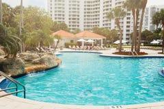 Palme di verde della noce di cocco sotto il sole, stagno con acqua blu, bello fondo tropicale Estate, turismo, feste, fotografie stock