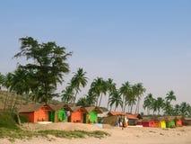 Palme e piccole pensioni su una spiaggia Immagini Stock