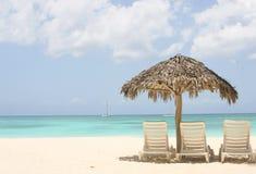 Palme und zwei Stühle auf Sand Stockbild