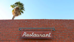 A palmeira eleva-se sobre um restaurante enquanto um sinal balança filme