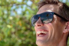 Palmeira, praia branca e água azul claro refletidas nos óculos de sol de um homem feliz maldives fotografia de stock