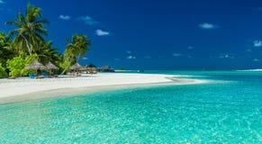 Palmen en strandumbrelllas over lagune en witte zandige beac Royalty-vrije Stock Afbeeldingen