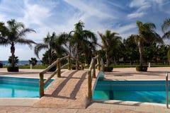 Palmen-Garten und Swimmingpool auf dem Strand Stockbilder