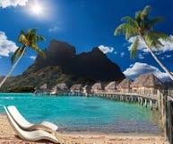Palmen, Strandstühle, Häuser auf Wasser und Meer. Stockfotografie