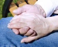 Palmen van gerimpelde handen van een bejaarde holding van mensen vrouwelijke hand royalty-vrije stock foto