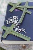 Palmenkreuz, Rosenkranzperlen, die auf einer Bibel sitzen stockfotos