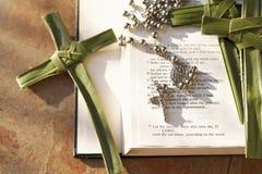 Palmenkreuz, Rosenkranzperlen, die auf einer offenen Bibel sitzen stockbild