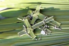 Palmenkreuze und -Rosenkranzperlen auf Palmblättern Stockbilder