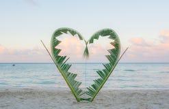 Palmenniederlassungen gebunden in die Form eines Herzens auf dem Strand Stockfotografie