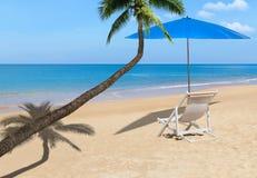 Palmera del coco con la silla de playa de madera blanca y parasol azul en la playa tropical Fotos de archivo