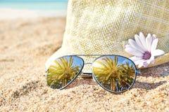 Palmeras en gafas de sol duplicadas elegantes en la arena contra el sombrero de paja Concepto tropical de las vacaciones de veran fotos de archivo
