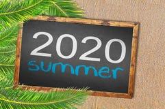 Palmeras y verano 2020 escritos en la pizarra Imagen de archivo libre de regalías