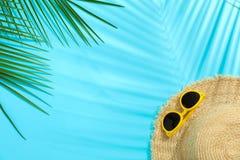 Palmettes, chapeau de paille et lunettes de soleil sur le fond de couleur, l'espace pour le texte photos libres de droits