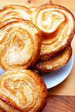 Palmier pastries. On white saucer, shot on wooden board background stock photos