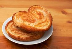 Palmier pastries on saucer. Palmier pastries on white saucer, shot on wooden board background Royalty Free Stock Photography