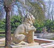 Palmiers et sculptures de lion en parc Image stock